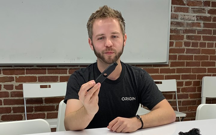 Origin founder Christopher Prucha holding a sample 3d printed part